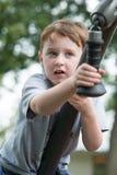 Den unga pojken som har den roliga yttersidan på, parkerar på en lekplatsklättringuppsättning fotografering för bildbyråer