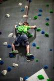 Den unga pojken som klättrar upp på övningsväggen in vaggar inomhus, idrottshall arkivbild