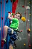 Den unga pojken som klättrar upp på övningsväggen in vaggar inomhus, idrottshall royaltyfri fotografi