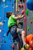 Den unga pojken som klättrar upp på övningsväggen in vaggar inomhus, idrottshall arkivfoton
