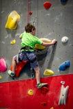 Den unga pojken som klättrar upp på övningsväggen in vaggar inomhus, idrottshall royaltyfri bild