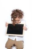 Den unga pojken som ner ser på tomt, kritiserar den svart tavlan Arkivbild