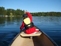 Den unga pojken som paddlar av en kanot på en skog, omgav framtill sjön Arkivbild