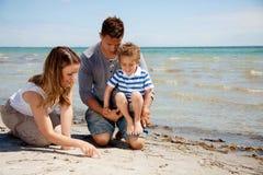Den unga pojken som ser som hans Mom, tecknar på sanden arkivfoto