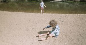Den unga pojken som sitter på en flodstrand, täcker sig med sand, ung flicka går förbi lager videofilmer