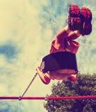 Den unga pojken som svänger i en lekplats, tonade med en retro tappning Royaltyfri Fotografi