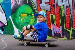 Den unga pojken som tar en vila på skridskon, parkerar Royaltyfri Fotografi