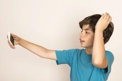 Den unga pojken tar en selfie Royaltyfria Foton