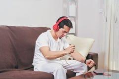 Den unga pojken tycker om att lyssna till musik arkivfoto