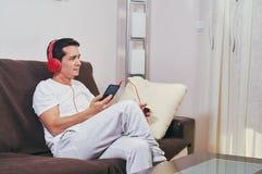 Den unga pojken tycker om att lyssna till musik arkivbild