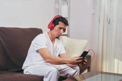 Den unga pojken tycker om att lyssna till musik royaltyfri foto