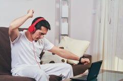 Den unga pojken tycker om att lyssna till musik arkivfoton