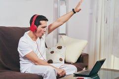 Den unga pojken tycker om att lyssna till musik royaltyfria foton