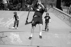 Den unga pojken, ungar parkerar, trick som rider sparkcykeln som högt hoppar i luft Arkivfoton