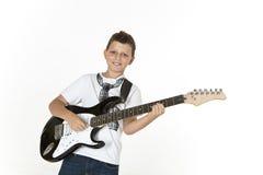 Den unga pojken vaggar på den elektriska gitarren Arkivfoto