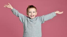 Den unga pojkeungen som hoppar i grå hoodie med händer, fördelade upp att skratta att le på rosa färger arkivbilder