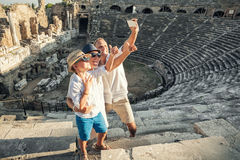 Den unga positiva familjen tar ett självfoto på den antika amphitheaen Royaltyfri Foto
