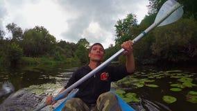 Den unga positiva mannen som paddlar kajaken, handlingkameran, aktiv vilar lager videofilmer