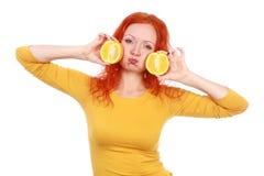 Den unga röda haired kvinnan som spelar med nya apelsiner, bär frukt arkivbild