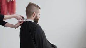 Den unga röda haired kvinnliga frisören klipper hår av den skäggiga manklienten lager videofilmer