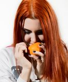 Den unga rödhårig mankvinnan äter citrus orange frukt som har gyckel royaltyfri bild