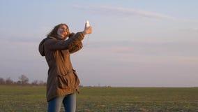 Den unga rödhåriga flickan gör en selfie med en smartphonekamera under vind lager videofilmer