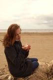 Den unga rödhåriga flickan sitter på ett fisknät och ser ett snäckskal i henne händer Royaltyfria Foton