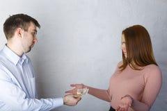 Den unga rödhåriga frun är olycklig med pengarna som hennes make ger henne med en skyldig framsida Det finansiella begreppet av f arkivfoton