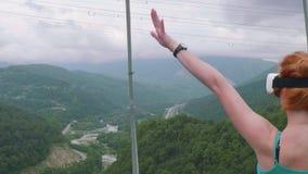 Den unga rödhåriga mannen i virtuell verklighetexponeringsglas kastar hennes hand upp mot bakgrund av den gröna skogsbevuxna berg lager videofilmer
