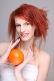 Den unga redhaired kvinnan med apelsinen i henne räcker Royaltyfri Bild