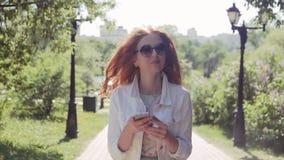 Den unga redhairlkvinnan som in går, parkerar med telefonen, ultrarapid stock video