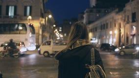 Den unga resande kvinnan med ryggsäcken som korsar trafikvägen, turisten som omkring ser och, finner vägen i aftonen Arkivbild