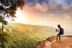 Den unga resande kvinnan med ryggsäckhatten och kameran står på överkanten av bergklippan som håller ögonen på härlig sikt av trä arkivfoton