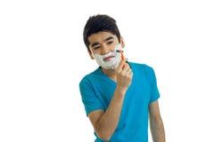Den unga roliga grabben med skum på hans framsida rakar hans skägg Fotografering för Bildbyråer