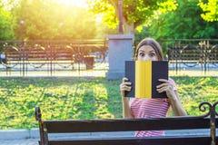 Den unga roliga kvinnan täcker hennes framsida med en bok på grund av känslaöverraskning och chock Emotionell flicka som rymmer e Arkivfoto