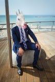 Den unga roliga mannen i elegant dräkt sitter på stadsstranden arkivbilder