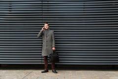 Den unga säkra affärsmannen i ett grå lag och portfölj i hans hand talar på mobiltelefonen mot väggen av modernt royaltyfria foton