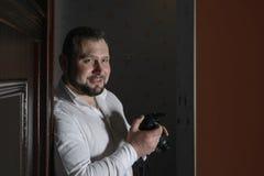 Den unga säkra manliga fotografen i en vit skjorta rymmer a Arkivfoto