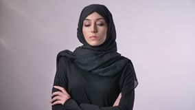 Den unga säkra muslimflickan i hijab korsar armar som håller ögonen på på kameran, det religiösa begreppet, grå bakgrund