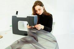 Den unga sömmerskakvinnan syr kläder på symaskinen arkivbild