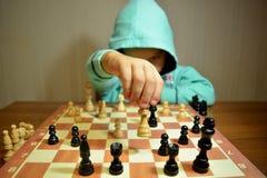Den unga schackspelaren spelar schack arkivbilder