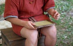 Den unga SCRIBEpojken skriver på en vaxminnestavla Royaltyfri Fotografi