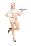 Den unga servitrisen i kort stavelse flåsar innehav ett tomt magasin Royaltyfri Foto