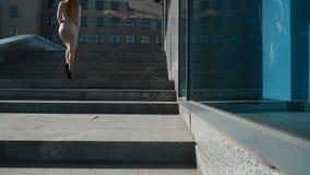 Den unga sexiga affärsflickan på höga häl går upp trappan arkivfilmer