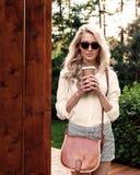 Den unga sexiga blonda flickan med långt hår i solglasögon med den bruna tappningpåsen som rymmer en kopp kaffe, har roligt och b Royaltyfria Foton