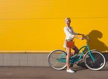 Den unga sexiga blonda flickan står nära tappninggräsplancykeln med den bruna tappningpåsen Royaltyfri Foto