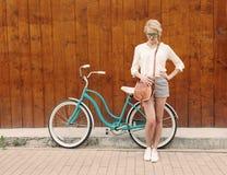 Den unga sexiga blonda flickan står nära tappninggräsplancykeln med den bruna tappningpåsen i grön solglasögon, varmt som tonning Arkivbild