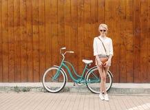 Den unga sexiga blonda flickan står nära tappninggräsplancykeln med den bruna tappningpåsen i orange solglasögon, varmt som tonni Arkivfoto