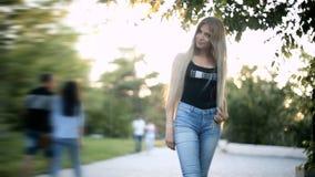Den unga sexiga blonda kvinnan som långt flödande hår går i parkerapanelljuset från solen, är glänsande arkivfilmer