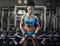 Den unga sexiga brunettflickan i idrottshallen som gör biceps, övar med skivstången Arkivbilder
